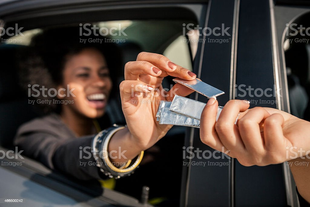 Women passing chewing gum out of the window car stock photo