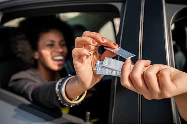 women passing chewing gum out of the window car - kauwgom stockfoto's en -beelden