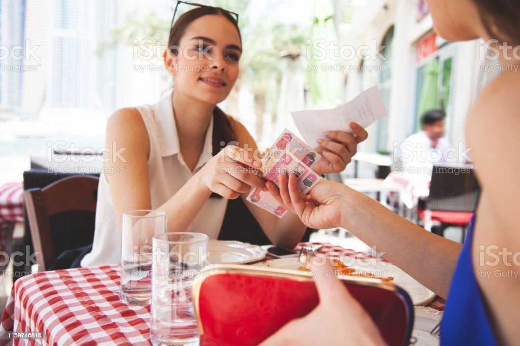 Women paying at the restaurant, splitting the check
