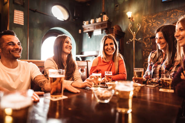 women people talking indoors in a pub with the beers stock photo