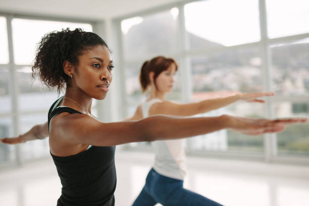 Women performing yoga in fitness studio African female fitness trainer performing yoga in warrior pose.  Woman stretching her arms at yoga class. Virabhadrasana. yoga class stock pictures, royalty-free photos & images