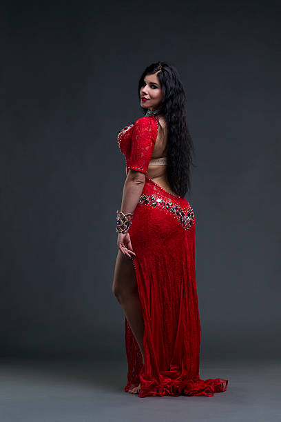 Women performs belly dance in red dress on gray background – Foto
