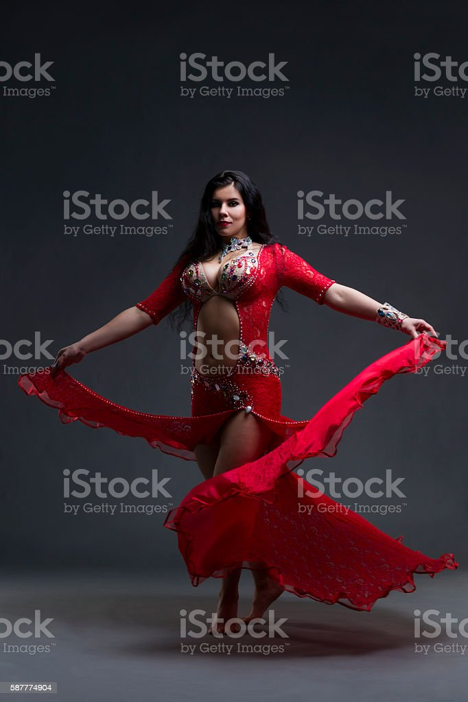 Women performs belly dance in red dress on gray background stock photo