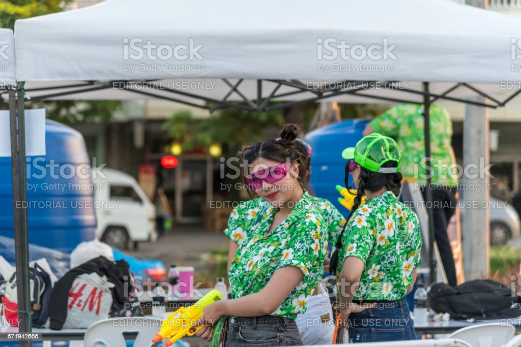 Women play and enjoying splashing with waters gun in Songkran Festival. stock photo