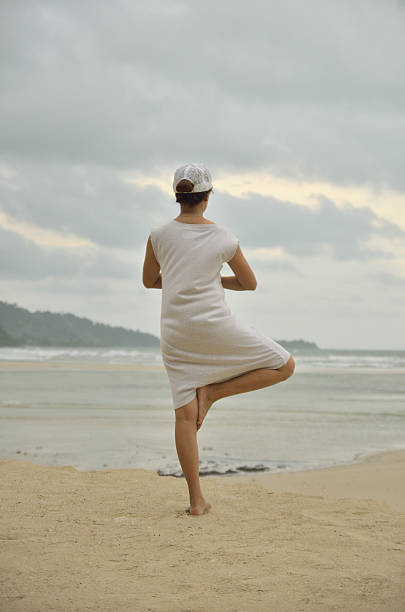 women play yoga on the bech stock photo