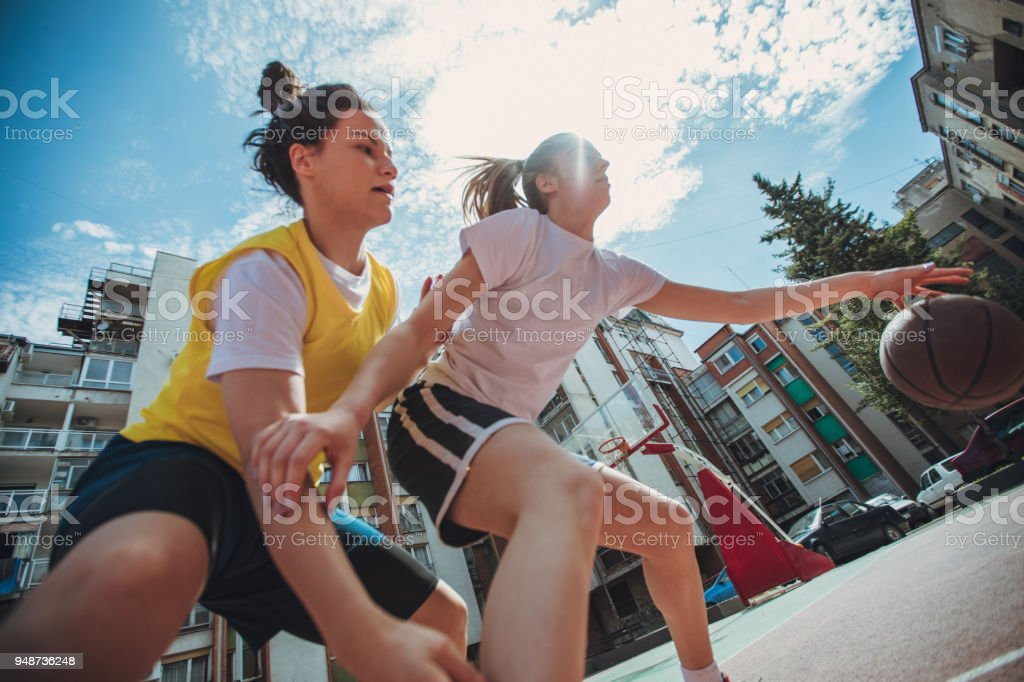 Women playing basketball on the playground stock photo
