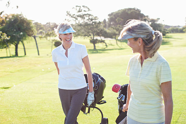 women playing golf - female golfer stock photos and pictures