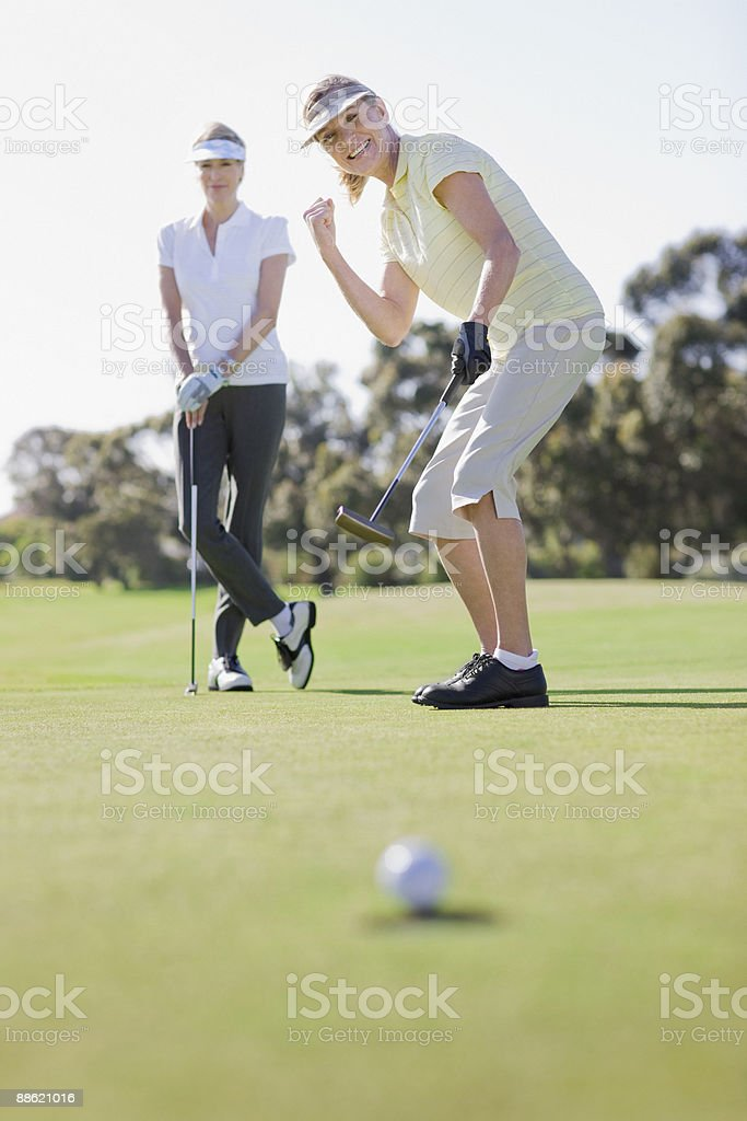 Women playing golf stock photo