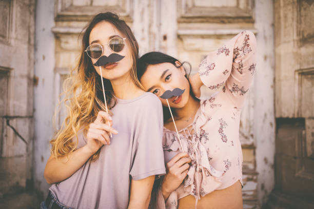Women playing with mustaches on sticks in city streets stock photo