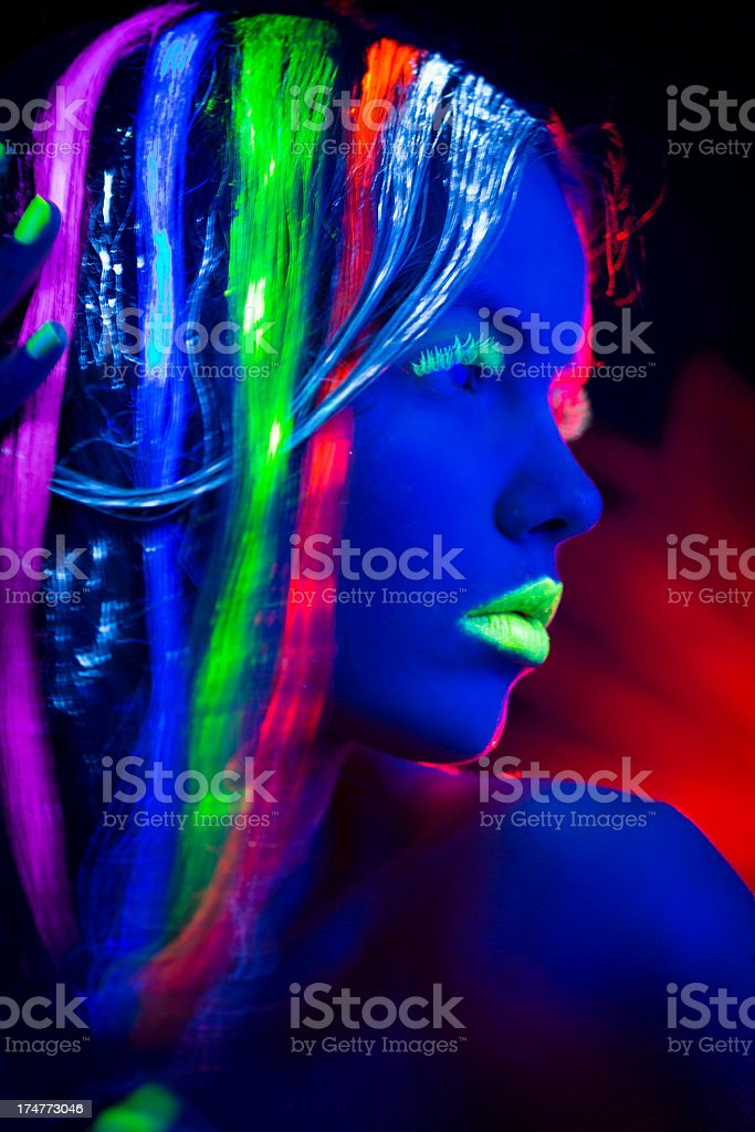 Women Portrait with Glowing Multi Colored Hair in black light royalty-free stock photo