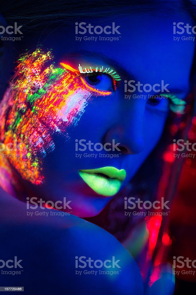 Women Portrait with Glowing Multi Colored makeup in black light stock photo