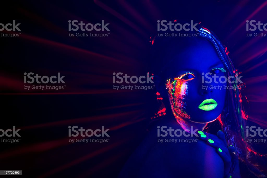 Women Portrait with Glowing Multi Colored makeup in black light royalty-free stock photo