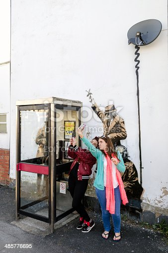 506166130 istock photo Women pose in front of a possible Banksy artwork, Cheltenham 485776695