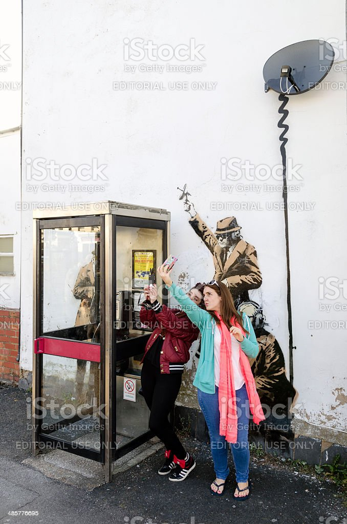 Women pose in front of a possible Banksy artwork, Cheltenham stock photo