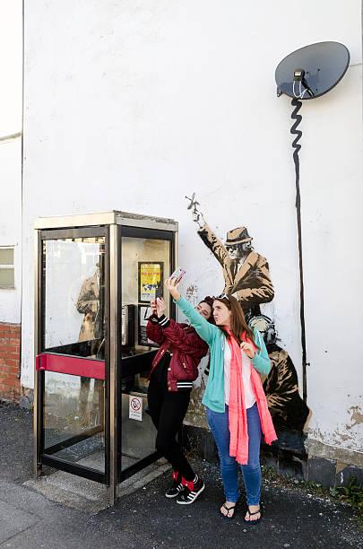 Donna in posa davanti a una possibile Banksy opere d'arte, Cheltenham - foto stock