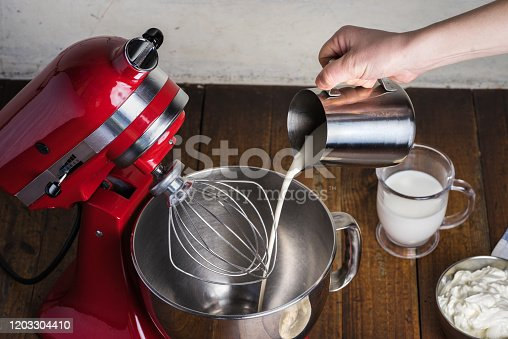 Open standing mixer with whisk on wooden table with ingredients