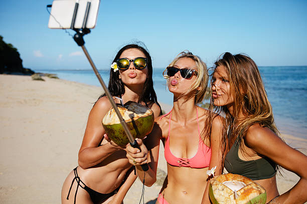 Women pouting for selfie on the beach Three young women in swimsuit on the beach enjoying holidays and taking self portrait selfie stick. Group of female friends with coconuts taking selfie on the sea shore. Pout for a selfie on beach. puckering stock pictures, royalty-free photos & images