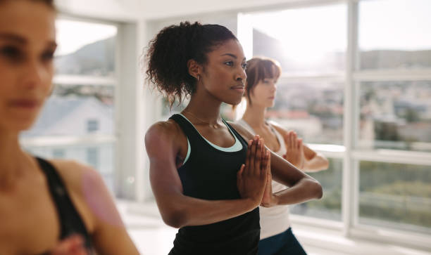 Women practices yoga in class Women stretching and practices yoga in class. Healthy female doing yoga workout in fitness studio. Standing with hands joined. yoga class stock pictures, royalty-free photos & images