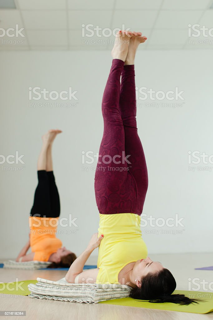 women practicing the Sarvangasana (Shoulder Stand stock photo