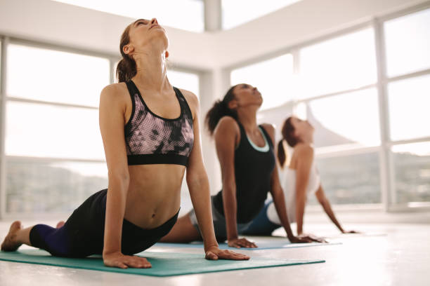 Women practicing yoga in fitness studio Young women practicing yoga. Fitness women meditating while doing cobra pose in gym. yoga class stock pictures, royalty-free photos & images