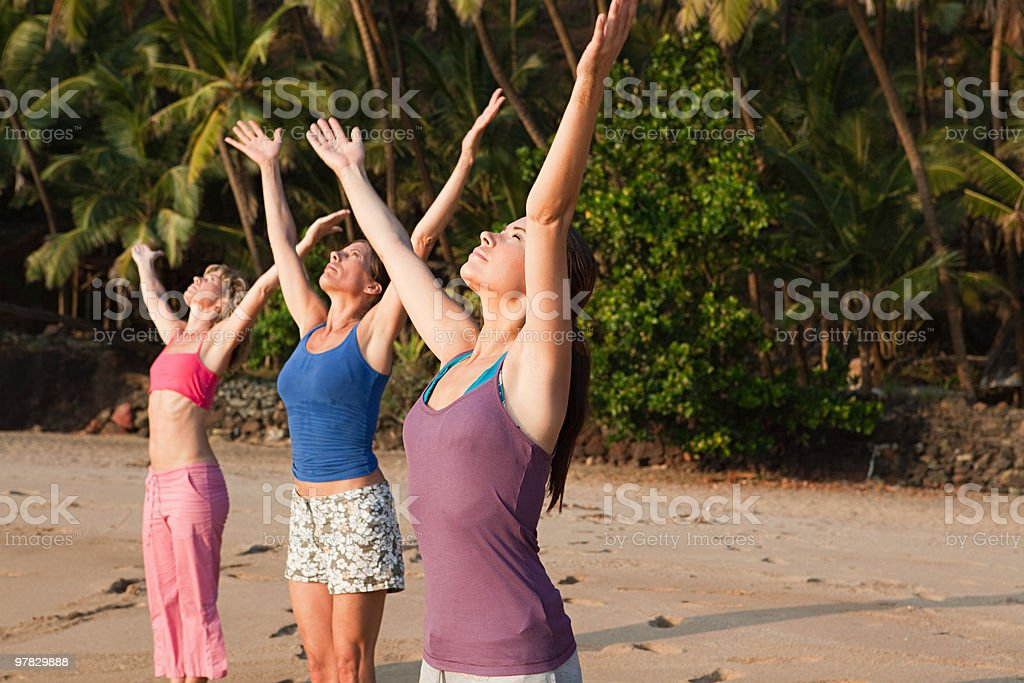 Women practicing yoga on a beach stock photo