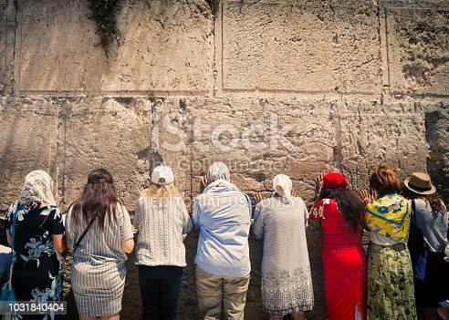Jerusalem, Israel - August 2018: Women praying at the Western Wall, which is one of Judaism most holy places and located in the old city of Jerusalem. The wall is cracked and in the cracks are pieces of paper with prayer notes.
