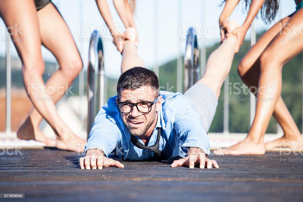 Women pulling a man on pool deck stock photo