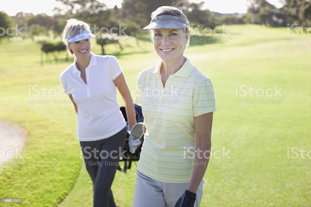 Women pulling golf carts royalty-free stock photo