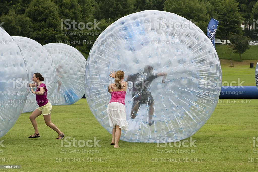Women Push Large Zorbs Around Grass Field At Summer Festival stock photo