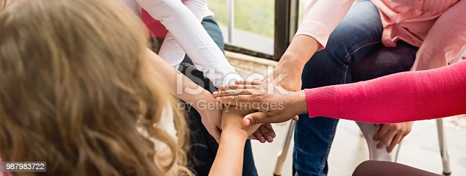 Multiethnic women in pink color theme put their hands together in breast cancer awareness campaign meeting, panoramic banner