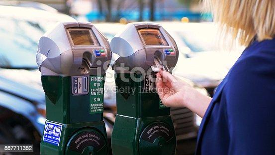Women putting credit card into parking meter.
