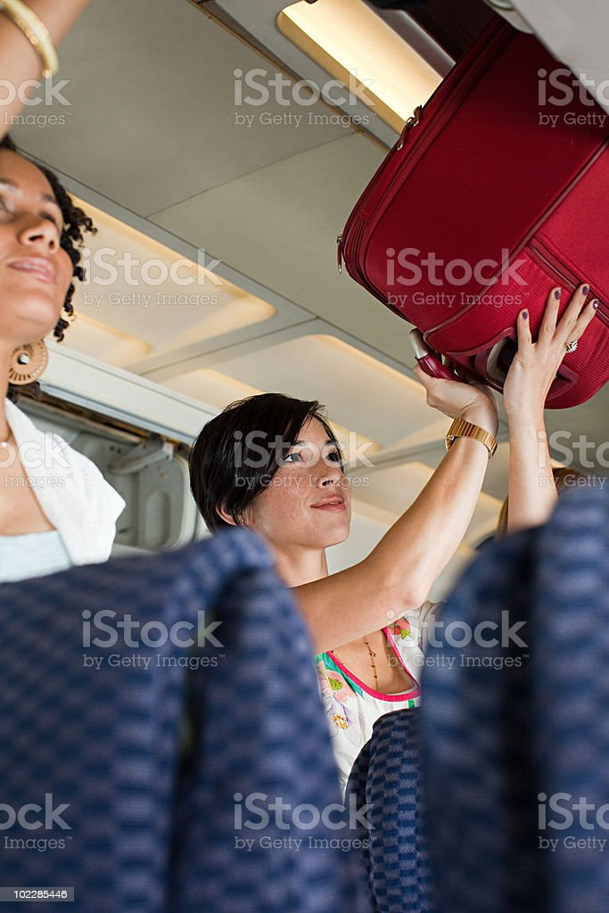 Women putting luggage in lockers on airplane stock photo