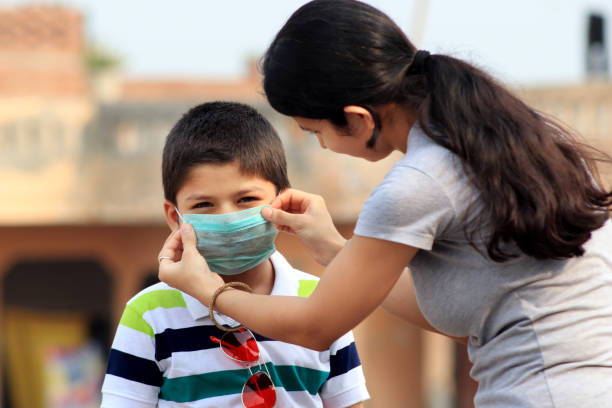 Women putting on medical mask to her child stock photo