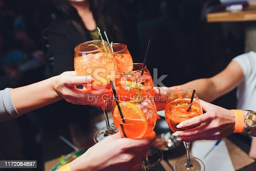 women raising a glasses of aperol spritz at the dinner table