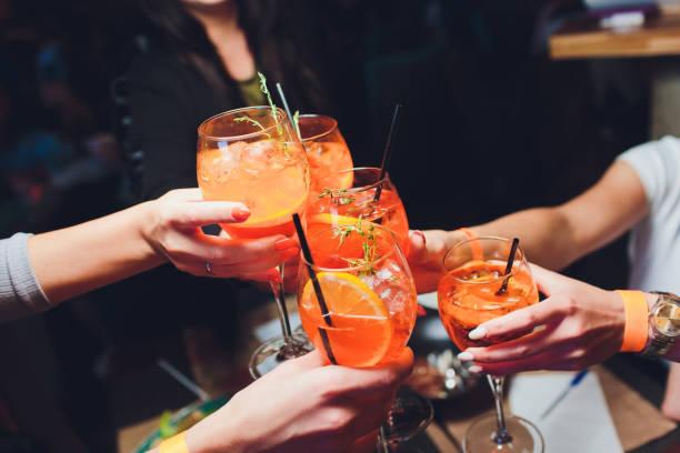 mujeres levantando unas copas de aperol spritz en la mesa de la cena. - cóctel bebida alcohólica fotografías e imágenes de stock