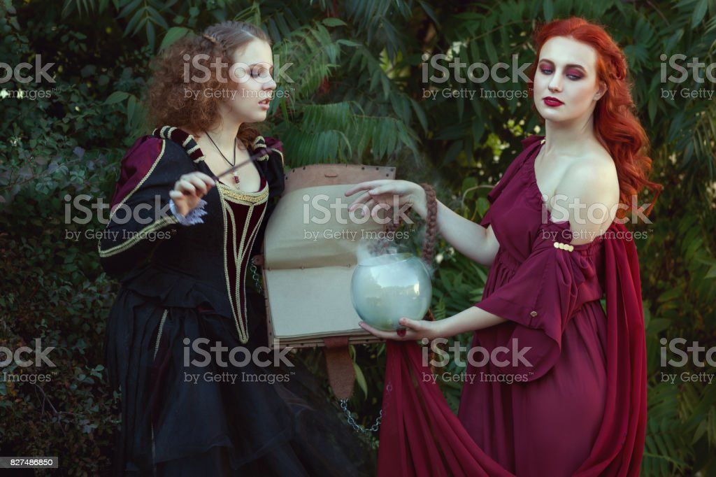 Women read a magic book and utter spells. stock photo