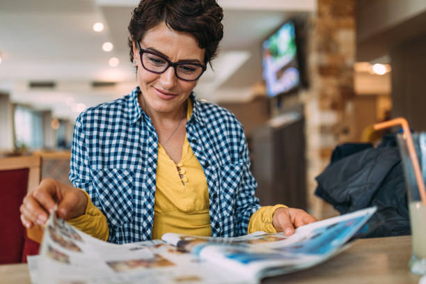 women reading a magazine - magazine stock photos and pictures