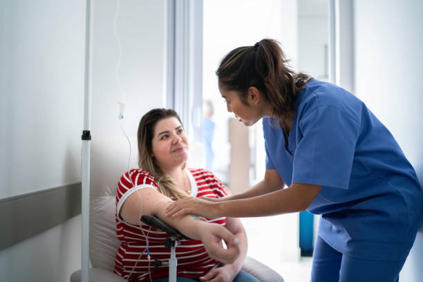 frauen erhalten iv tropfbehandlung - chemotherapie stock-fotos und bilder