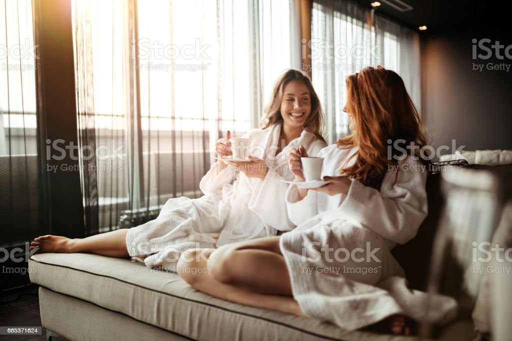 Women relaxing and drinking tea in robes during wellness weekend stock photo