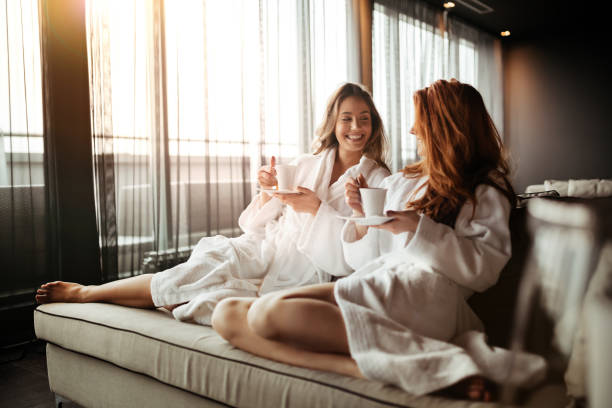 women relaxing and drinking tea in robes during wellness weekend - guest stock pictures, royalty-free photos & images