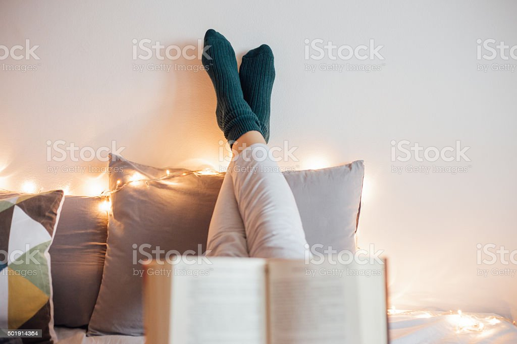 Women relaxing in bad and reading a book