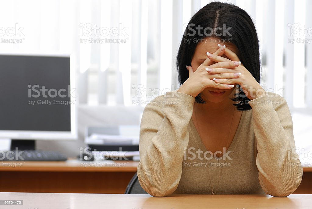 Women resting forehead against intertwined hands in office stock photo