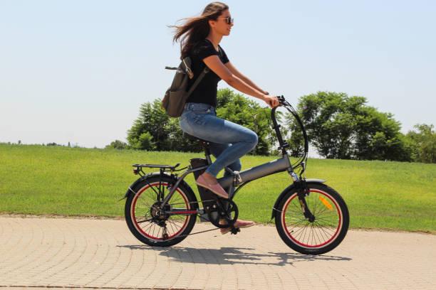 ein frauen reiten auf elektrische e-fahrrad im park - elektrorad stock-fotos und bilder