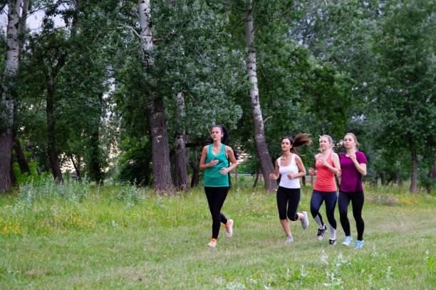 Women running in field stock photo