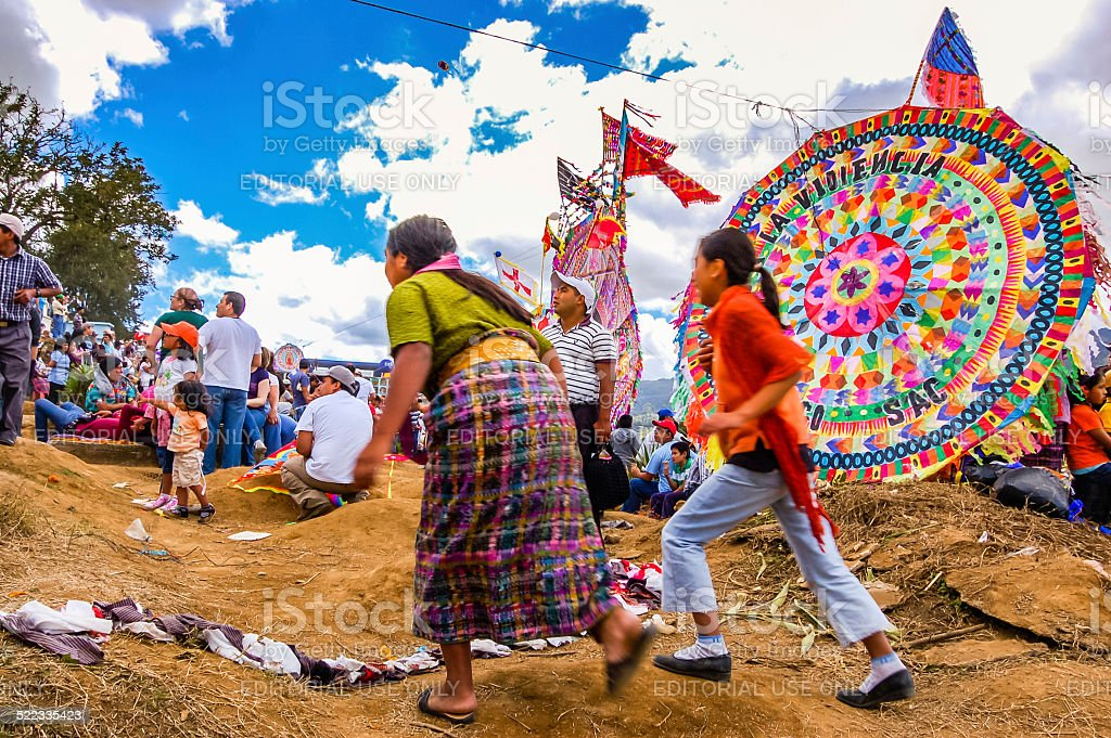 Women running in front of kite, All Saints' Day, Guatemala stock photo