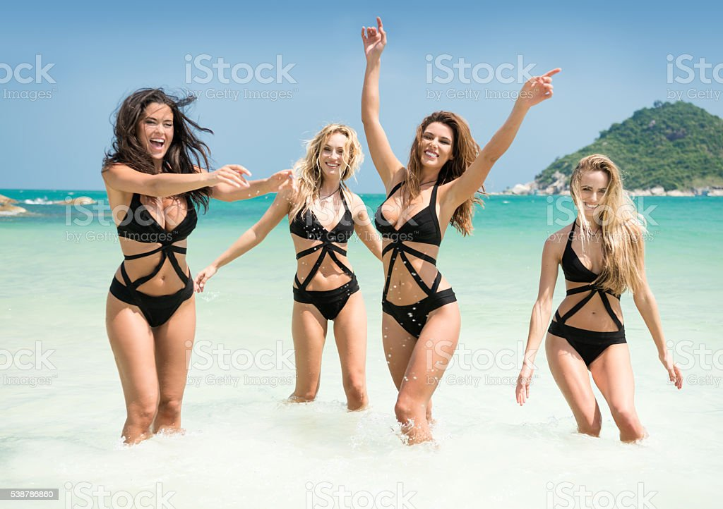 Women running, splashing in the Ocean on Vacation stock photo