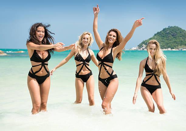 Women running, splashing in the Ocean on Vacation stock photo