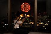 女性はアパートの窓から花火を見る