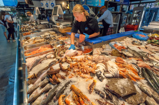 women selling marine reptiles, fish, crayfish, octopuses and other sea products on the urban food market - banchi di pesci foto e immagini stock