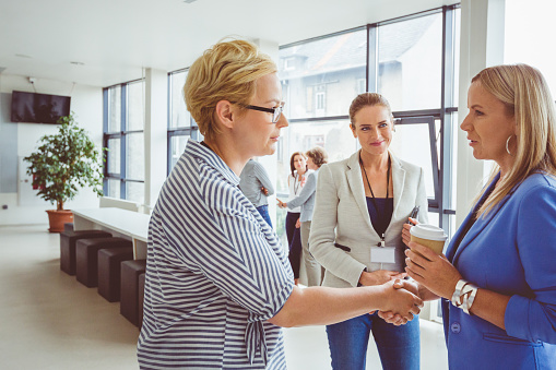 Women Shaking Hands During A Break In Seminar Stock Photo - Download Image Now